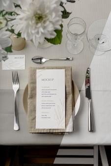Vue de dessus de la maquette du menu de printemps sur une assiette avec des couverts et des verres
