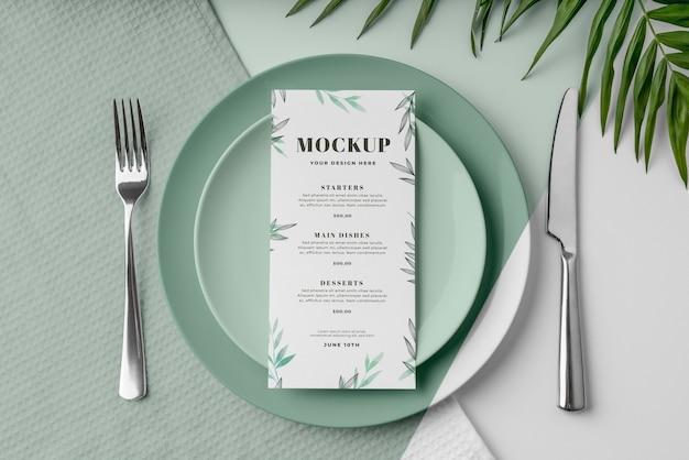 Vue de dessus de la maquette du menu de printemps sur des assiettes avec des feuilles et des couverts