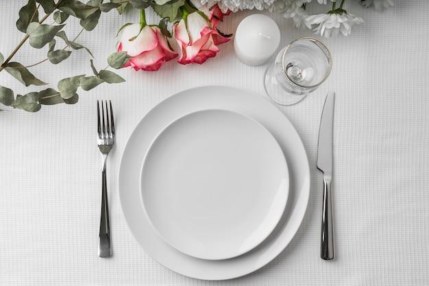 Vue de dessus de la maquette du menu de printemps sur des assiettes avec des fleurs et des couverts