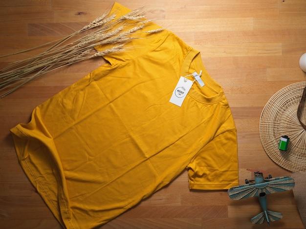 Vue de dessus de la maquette de t-shirt jaune avec maquette d'étiquette de prix sur la table en bois avec des décorations