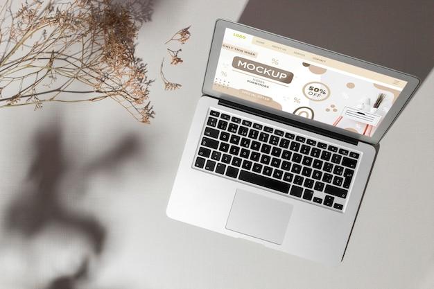 Vue de dessus ordinateur portable ouvert avec maquette d'écran à côté des feuilles