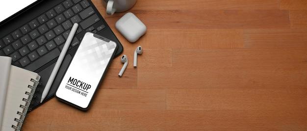 Vue de dessus de la table en bois avec maquette de smartphone