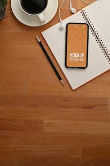 Vue de dessus de la table en bois avec smartphone, ordinateur portable, crayon et espace de copie