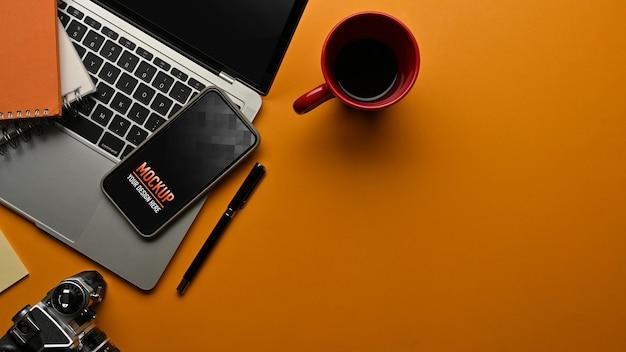 Vue de dessus de la table de travail avec maquette d'ordinateur portable et de smartphone