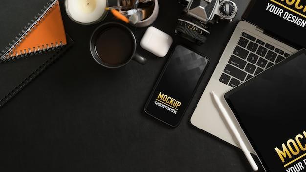 Vue de dessus de la table de travail avec maquette de smartphone, tablette, ordinateur portable, fournitures et espace de copie