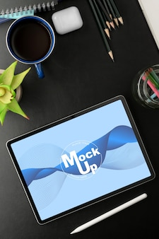 Vue de dessus de la table de travail noire avec maquette de tablette, fournitures de bureau et accessoires