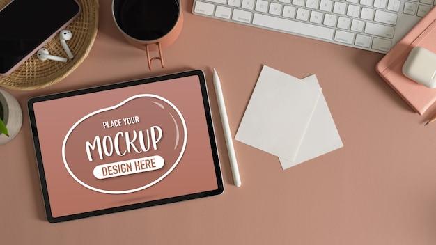Vue de dessus de la table de travail rose avec maquette de tablette, bloc-notes, accessoires, fournitures et tasse à café