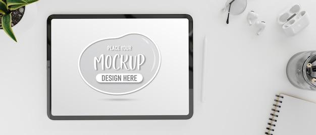 Vue de dessus de la tablette numérique avec écran de maquette sur un espace de travail de concept blanc avec papeterie