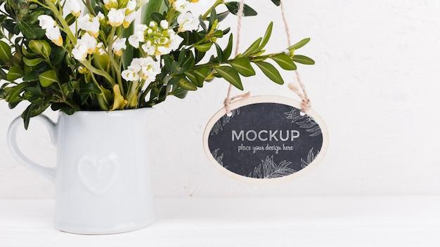 Vue de face de l'arrangement de fleurs avec maquette de signe