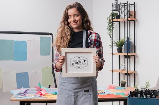 Vue de face de l'artiste féminine tenant le cadre