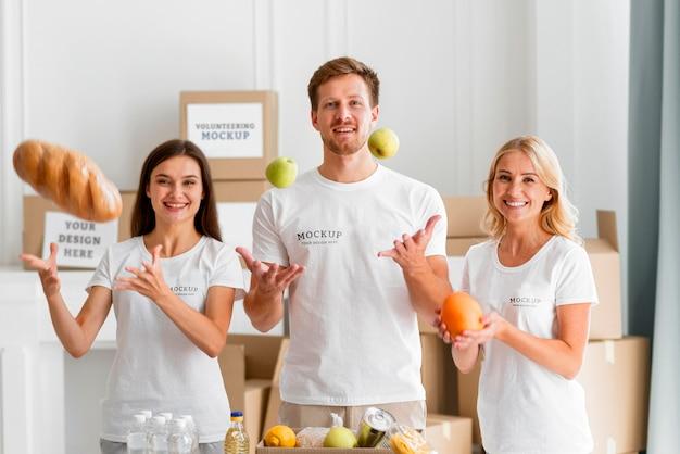 Vue de face de bénévoles smiley préparer des boîtes avec de la nourriture pour le don