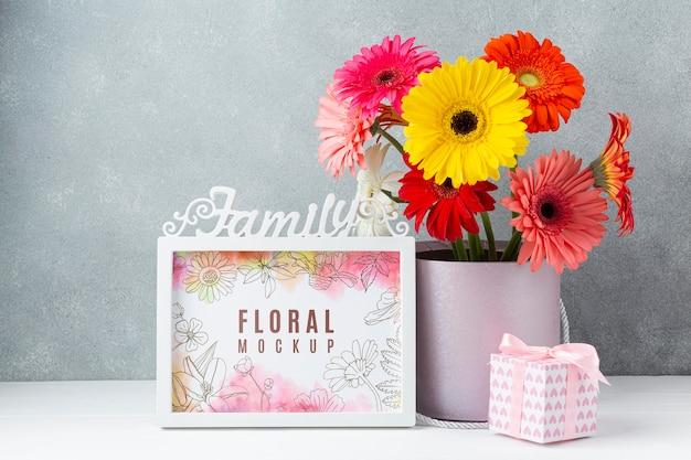 Vue de face du bouquet de marguerites avec cadre et cadeau