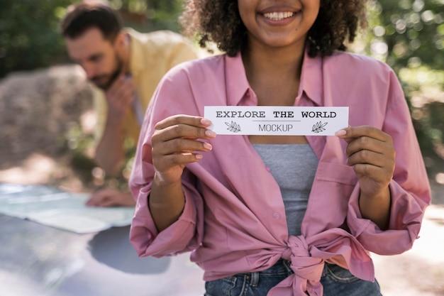 Vue de face du camping femme smiley et tenant un morceau de papier