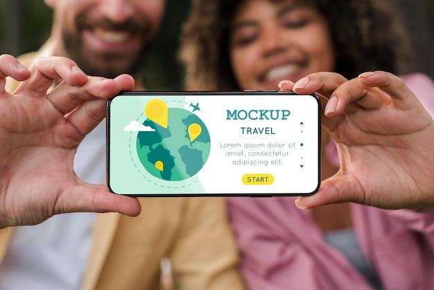 Vue de face du couple souriant tenant le smartphone en camping