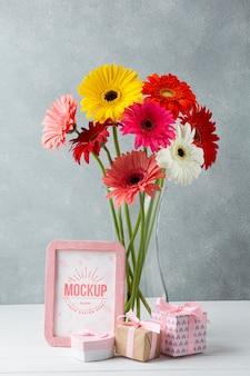 Vue de face du vase avec des marguerites avec cadre et cadeaux