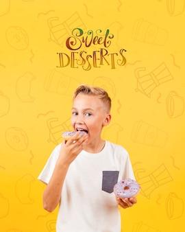 Vue de face d'un enfant mangeant un beignet