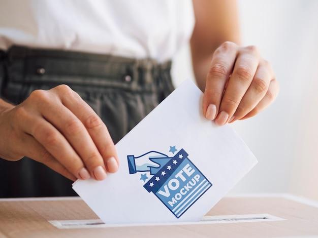 Vue de face femelle mettant la maquette du bulletin de vote dans la boîte
