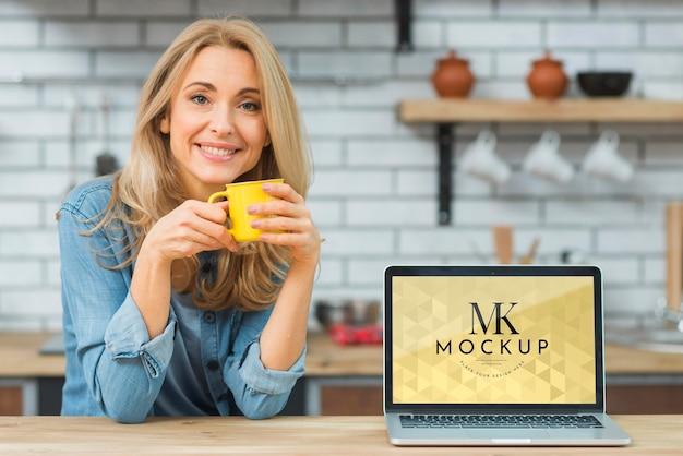 Vue de face de la femme dans la cuisine avec café et ordinateur portable