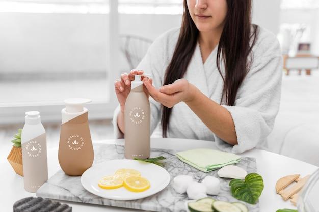 Vue de face de la femme à la maison à l'aide d'un hydratant