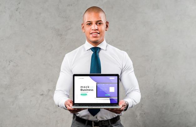Vue de face homme tenant un ordinateur portable