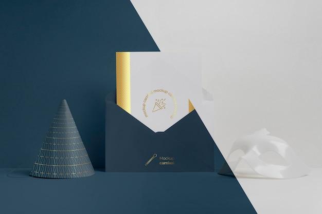 Vue de face de l'invitation de carnaval minimaliste dans une enveloppe avec cône et masque
