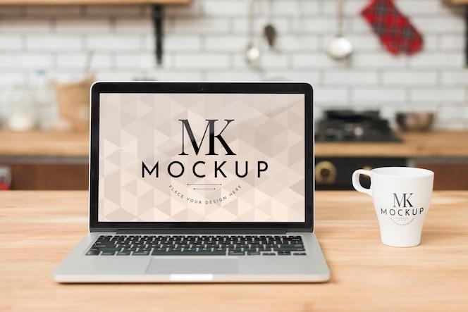 Vue de face de l'ordinateur portable dans la cuisine avec une tasse de café