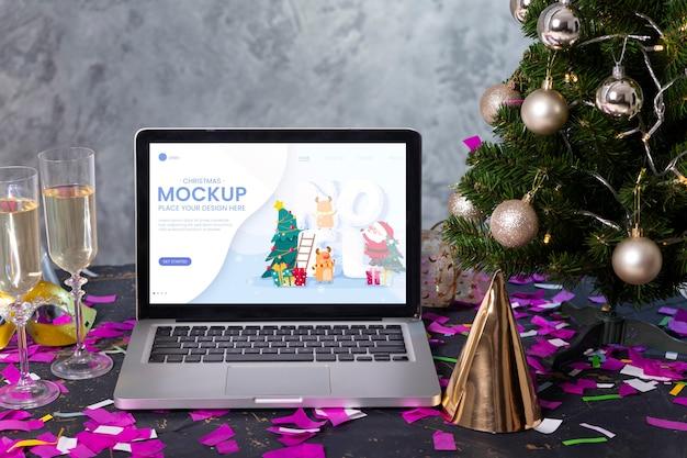 Vue de face de l'ordinateur portable avec des verres de champagne et chapeau de fête pour la célébration du nouvel an