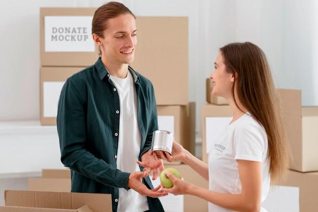 Vue latérale du bénévole distribuant des provisions à l'homme