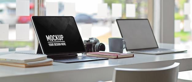 Vue latérale du bureau de la table de travail avec maquette de tablette numérique