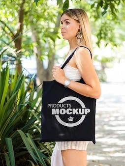Vue latérale femme blonde tenant une maquette de sac noir