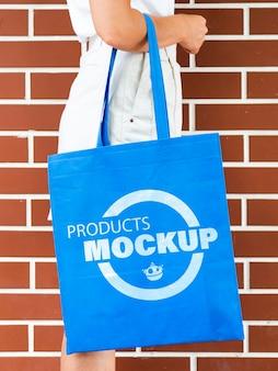 Vue latérale femme tenant une maquette de sac bleu uni