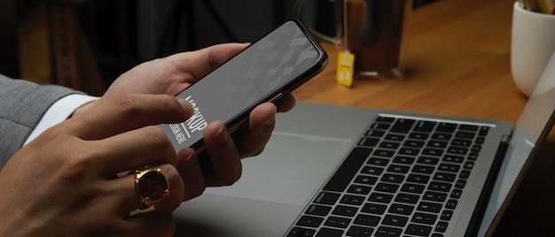 Vue latérale de la main masculine à l'aide de la maquette du smartphone