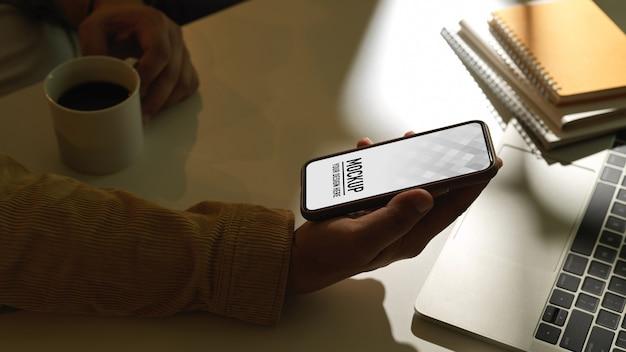 Vue latérale de la main masculine tenant le smartphone sur l'espace de travail avec ordinateur portable et ordinateurs portables