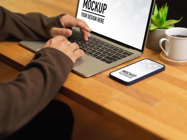 Vue latérale des mains mâles tapant sur une maquette d'ordinateur portable