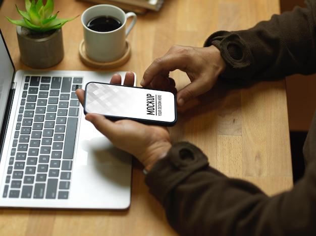 Vue latérale des mains mâles tenant la maquette du smartphone