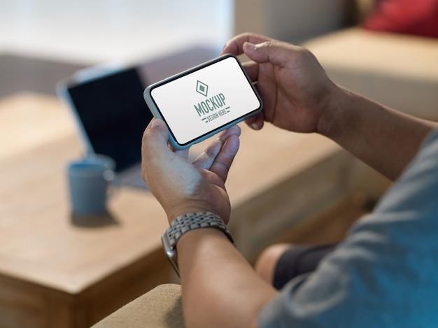 Vue latérale des mains mâles tenant une maquette de smartphone horizontal tout en vous relaxant dans le salon
