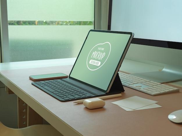 Vue latérale d'une maquette de tablette numérique sur un bureau d'ordinateur avec smartphone et accessoires