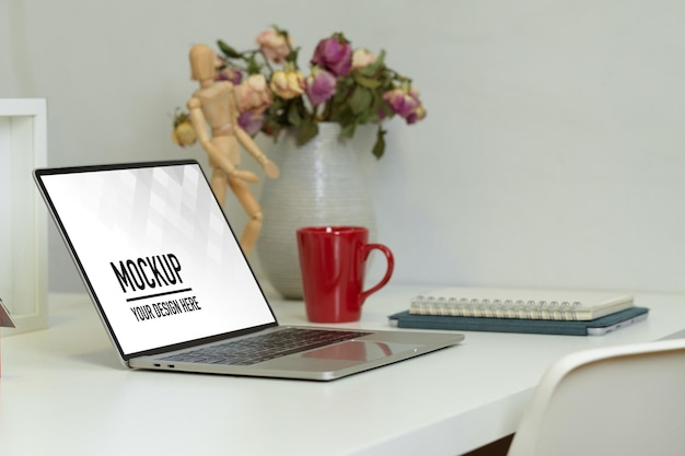 Vue latérale de la table de travail avec maquette d'ordinateur portable
