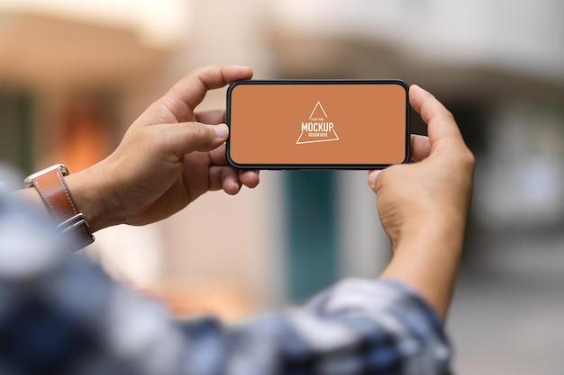 Vue Rapprochée D'un Homme Mains Tenant Une Maquette De Smartphone PSD Premium