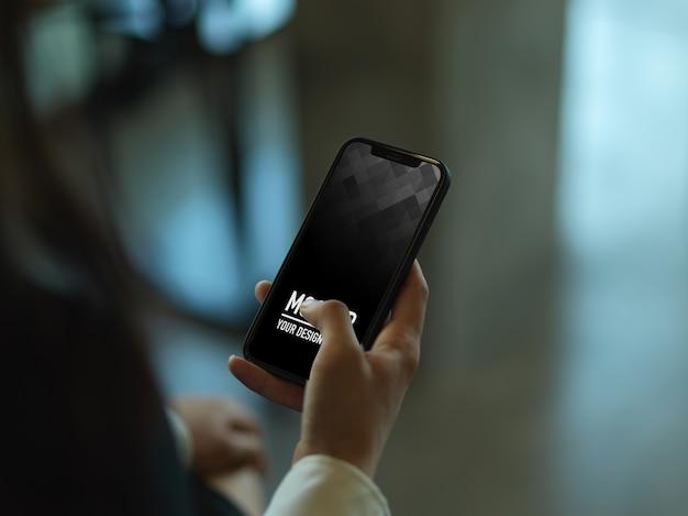 Vue rapprochée de la main féminine à l'aide de la maquette du smartphone