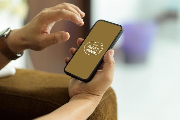 Vue rapprochée de la main masculine à l'aide de la maquette du smartphone