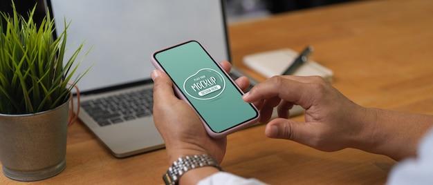 Vue rapprochée de la main masculine à l'aide d'une maquette de smartphone sur une table de travail avec une maquette d'ordinateur portable et de papeterie