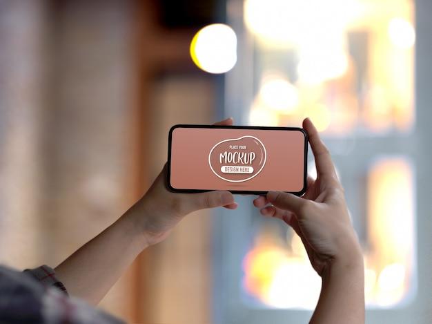 Vue rapprochée des mains féminines tenant la maquette de l'écran du smartphone horizontal