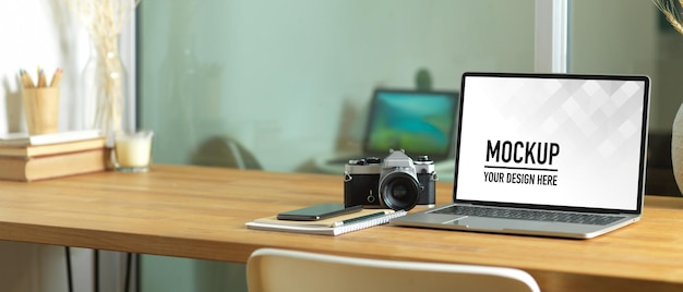 Vue rapprochée de la table de travail avec maquette d'ordinateur portable