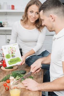 Woman holding book dans la cuisine pendant que l'homme cuisine