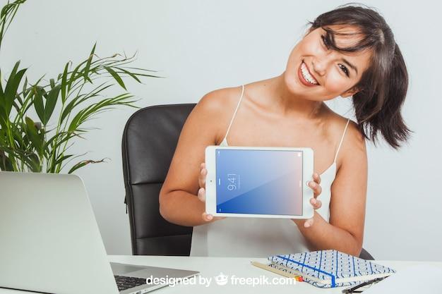 A maquete de tablet, escritório e mulher feliz