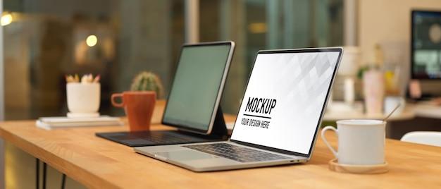 A maquete do laptop e as xícaras de café na mesa de madeira da sala de escritório incluem