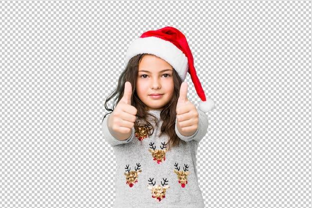 A menina que comemora o dia de natal com polegares levanta, felicidades sobre algo, apoia e respeita o conceito.