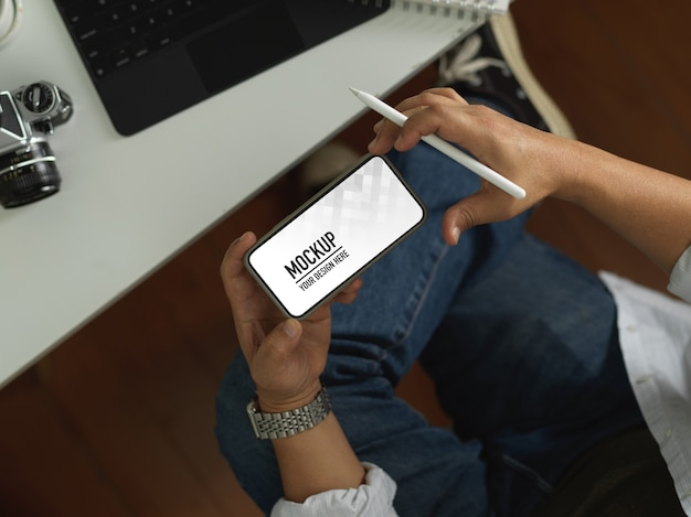 A vista superior de uma mão masculina usando um smartphone horizontal inclui um traçado de recorte enquanto segura uma caneta stylus