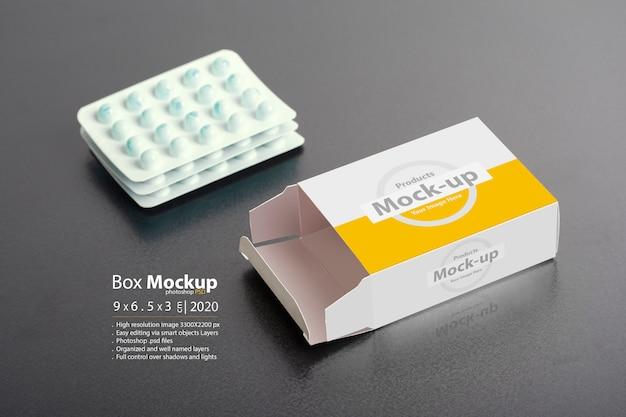 Abriu a caixa de comprimidos com pedaços de comprimidos em fundo escuro